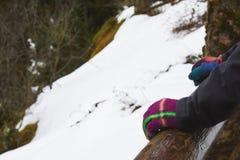 Женщина рук в зиме перчаток зимы, на деревянной загородке с sn Стоковое фото RF