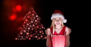 Женщина Санта смотря в сумке подарка и рождественская елка снежинки делают по образцу форму Стоковые Фотографии RF
