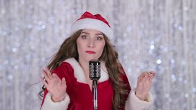 Женщина Санты поет в ретро микрофоне нот bokeh предпосылки замечает тематическое конец вверх сток-видео