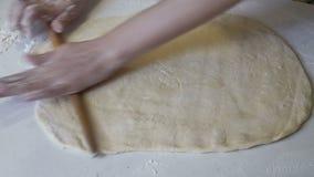 Женщина свертывает вне тесто на белой таблице с деревянной вращающей осью акции видеоматериалы
