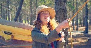 Женщина связывая гамак в лесе 4k видеоматериал