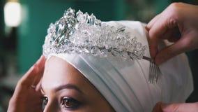 Женщина связывая исламский тюрбан свадьбы для красивой модели Стоковое фото RF