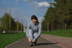 Женщина связывая шнурки ботинка Женский бегун фитнеса спорта получая готовый для jogging outdoors на пути леса весной или лете стоковое фото