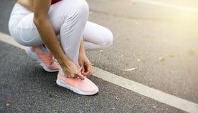 Женщина связывая шнурки ботинка Стоковые Фотографии RF