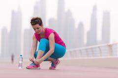 Женщина связывая шнурки на тапках Стоковая Фотография