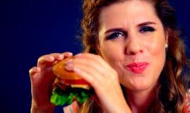 Женщина сдерживает бургер и подмигивает Счастливый студент ест обед сандвича стоковые изображения