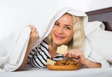 Женщина секретно есть печенья в кровати Стоковое фото RF