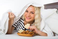 Женщина секретно есть печенья в кровати Стоковое Фото