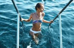 Женщина сексуального бикини усмехаясь приходя из воды держа на поручни Молодая модель с тонким телом потери веса стоковые фотографии rf