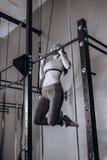 Женщина сексуальных детенышей подходящая делая тягу-вверх дальше на поперечной балке - турнике Сильный женский фитнес на спортзал стоковые изображения rf