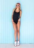 Женщина сексуального swag белокурая в bodysuit при солнечные очки и крышка совершенного тела нося представляя около стены стоковые изображения