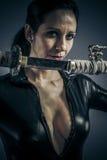 Женщина сексуальной девушки воинская представляя с оружи. стоковое фото