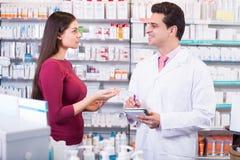 Женщина сервировки аптекаря в фармации Стоковое Фото
