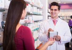 Женщина сервировки аптекаря в фармации Стоковые Изображения