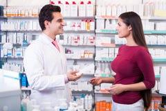 Женщина сервировки аптекаря в фармации Стоковое Изображение