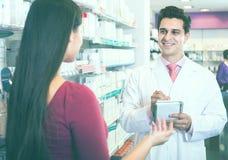 Женщина сервировки аптекаря в фармации Стоковая Фотография