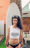 Женщина серфера брюнет с удерживанием верхней части и бикини Стоковое Изображение