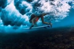 Женщина серфера с пикированием доски прибоя под водой с вниз большой разбивая волной стоковые изображения rf