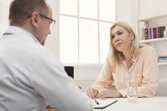 Женщина серьезного доктора советуя с в больнице стоковая фотография