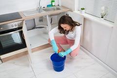 Женщина сжимая влажную ветошь на комнате кухни Стоковая Фотография