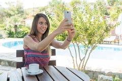 Женщина сидит близко бассейном на временени принимая чай Bozcaada Canakkale кофе питья фото Selfie в Турции 2017 Стоковое фото RF
