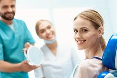 Женщина сидит в зубоврачебном стуле Прежде чем она стойки доктор и владения зеркало в ее руках Около медсестры Стоковая Фотография RF