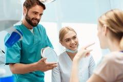 Женщина сидит в зубоврачебном стуле Прежде чем она стойки доктор и владения зеркало в ее руках Около медсестры Стоковое Изображение RF