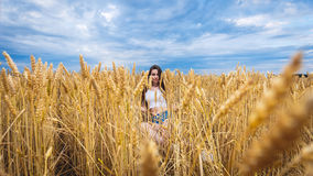 Женщина сидит в поле пшеницы и наслаждается природой Стоковое фото RF