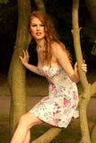 Женщина сидит на дереве Стоковые Фото