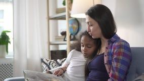 Женщина сидит на диване и читает историю хвоста маленькой милой девочк акции видеоматериалы