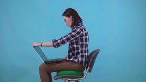 Женщина сидит на протезной подушке на стуле на голубой предпосылке, концепции геморроев сток-видео