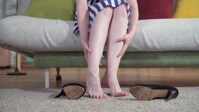 Женщина сидит на софе принимает пятки и делает массаж ноги сток-видео