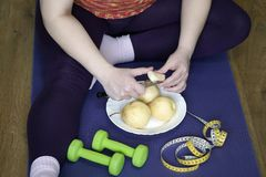 Женщина сидит на спорт половик и режет грушу стоковое фото rf