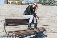 Женщина сидит на стенде в джинсах стоковые изображения