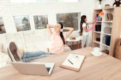 Женщина сидит на таблице около компьтер-книжки и отдыхает ее ноги на таблице Стоковая Фотография