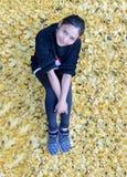Женщина сидит на упаденные листья в осени Стоковое Изображение
