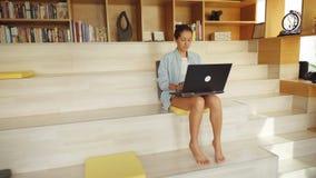 Женщина сидя босоногая деятельность на ее ноутбуке акции видеоматериалы