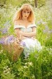 Женщина сидя весной луг Стоковое Изображение RF