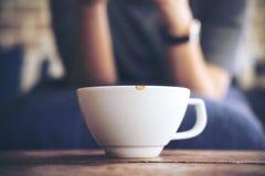 Женщина сидя в кафе с белой чашкой керамики горячего кофе на винтажном деревянном столе в кафе Стоковое Изображение RF