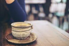 Женщина сидя в кафе с чашкой керамики горячего кофе на винтажном деревянном столе в кафе Стоковое Изображение RF