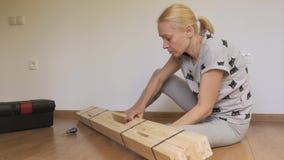Женщина сидя в комнате на поле распаковывает деревянный шкаф купленный в магазине Собрание мебели сток-видео