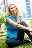 Женщина сидя в парке с городом в предпосылке Стоковая Фотография