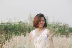Женщина сидя в поле травы стоковая фотография