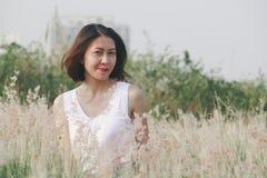 Женщина сидя в поле травы стоковые фото