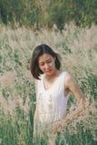 Женщина сидя в поле травы стоковое фото rf