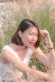 Женщина сидя в поле травы стоковые изображения