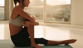 Женщина сидя в представлении йоги на студии фитнеса Стоковые Фото