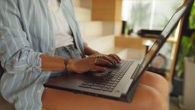 Женщина сидя и работая на ее ноутбуке акции видеоматериалы