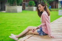 Женщина сидя на бамбуковом мосте стоковые изображения