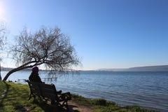 Женщина сидя на банке морем стоковое фото